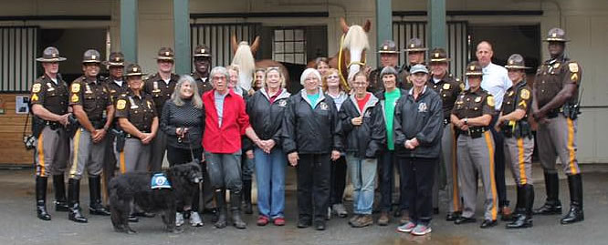 Group photo of the Friends of the Mounted Patrol and Mounted Patrol Unit at their courtyard home at Carousel Park